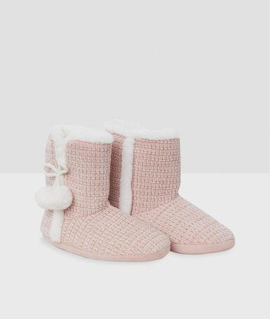 Zapatillas tipo botines con pompones rosa.