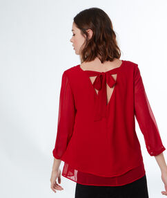 Blouse avec nœud au dos rouge.