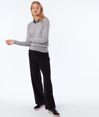 Pantalón ancho con cinturón negro.